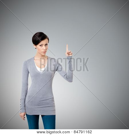 Young girl shows forefinger, attention sign, isolated on grey