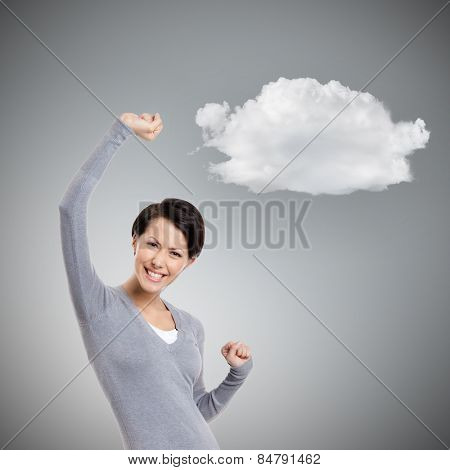 Beautiful girl gestures triumphal fists, isolated on grey background with cloud