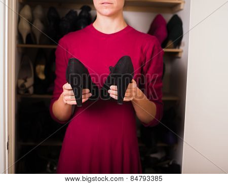 Woman With Pair Of Shoes At Home