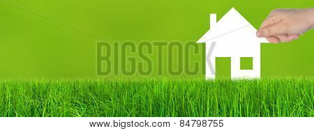 Concept or conceptual white paper house symbol held in hand by a woman in green summer grass background, metaphor to construction, eco, ecology, loan, mortgage, property, business, investment or home