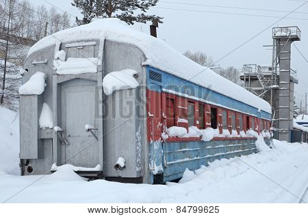 Old rusty passenger wagon piled high with snow