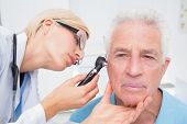 stock photo of otoscope  - Female doctor examining senior patients ear with otoscope in clinic - JPG