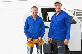 pic of handyman  - Smiling handymen looking at camera in front of their van - JPG