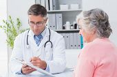 stock photo of prescription  - Male doctor explaining prescriptions to senior woman in clinic - JPG