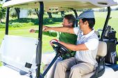stock photo of buggy  - Golfing friends driving in their golf buggy at the golf course - JPG