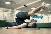 image of fitness  - Fit man doing pilates in fitness studio against fitness interface - JPG