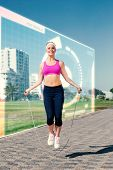 image of skipping rope  - Fit blonde skipping rope on the pier against fitness interface - JPG
