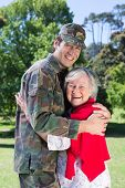 stock photo of reunited  - Soldier reunited with his mother on a sunny day - JPG