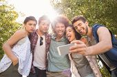 stock photo of friendship day  - Happy friends in the park taking selfie on a sunny day - JPG