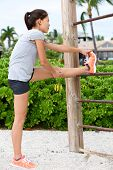picture of crossed legs  - Fit fitness woman doing stretching exercises outdoors on beach - JPG