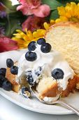 image of pound cake  - Slice of pound cake with whipped cream topped with blueberries and flowers in the background - JPG