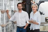 foto of warehouse  - Smiling warehouse managers checking inventory in a large warehouse - JPG