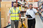 picture of warehouse  - Worker walking with his manager over the phone in warehouse - JPG