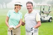 foto of buggy  - Happy golfing couple with golf buggy behind on a foggy day at the golf course - JPG