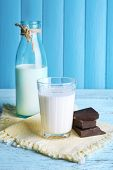 stock photo of bittersweet  - Glass and bottle of milk with chocolate chunks on color wooden planks background - JPG