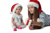 stock photo of santa baby  - baby girl and woman in Santa Claus hat with christmas gift box - JPG