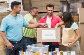 pic of warehouse  - Warehouse workers packing up donation boxes in a large warehouse - JPG
