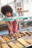 picture of over counter  - Smiling employee moving over the pastry at the bakery - JPG