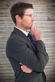 stock photo of frown  - Frowning businessman thinking against wooden planks background - JPG