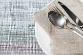 stock photo of sackcloth  - Empty white plate spoon fork knife on sackcloth background - JPG