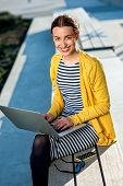 stock photo of work bench  - Young woman in yellow sweater working with laptop and phone on the bench in the city - JPG