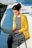 pic of work bench  - Young woman in yellow sweater working with laptop and phone on the bench in the city - JPG