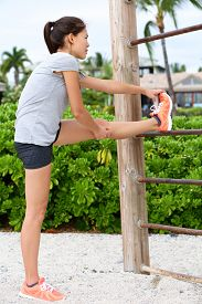 pic of crossed legs  - Fit fitness woman doing stretching exercises outdoors on beach - JPG