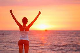 pic of celebrate  - Happy cheering celebrating success woman at beautiful beach sunset - JPG