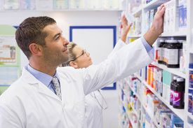 image of pharmaceuticals  - Team of pharmacists looking at medicine at the hospital pharmacy - JPG