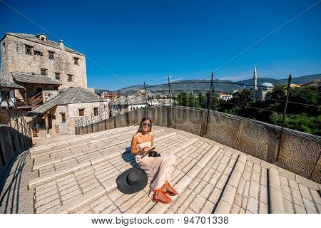 Woman sitting on the old bridge in Mostar city
