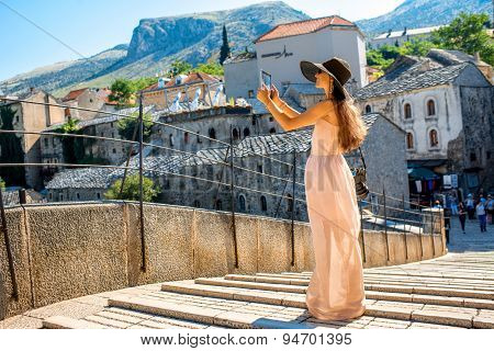 Woman photographing city view in Mostar