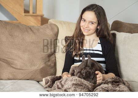 Young girl stroking his pet rabbit at home.