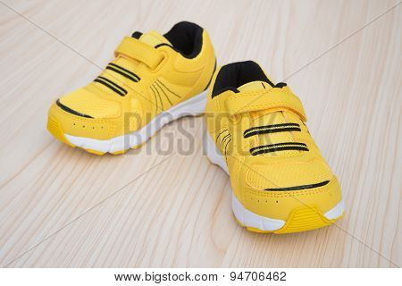 Pair Of Yellow Sporty Shoes For Kid On A Wood Background