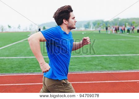 Fast running fit man in blue clothes with football field on background