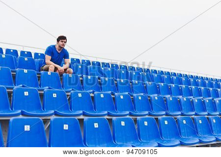 Young man athlete in blue shirt sitting on row of blue seats on stadium