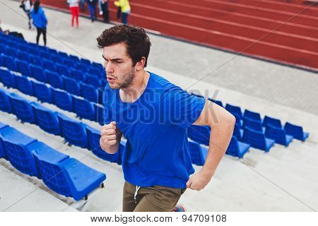 Attractive man model running upstairs stressed between seats on a stadium during workout training