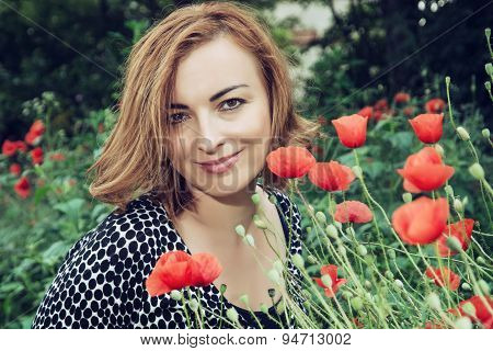 Young Caucasian Brunette Woman And Corn Poppy Flowers