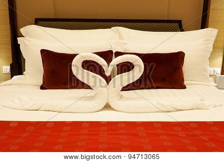 Hotel room with towel forming heart shape