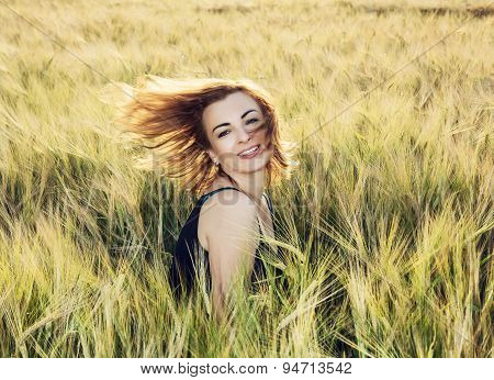 Young Woman Throws Her Hair In Wheat Field By Sunset