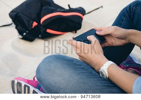 Woman In Jeans Sitting On The Beach Sand Cross-legged And Using A Mobile Phone With A Touch Screen