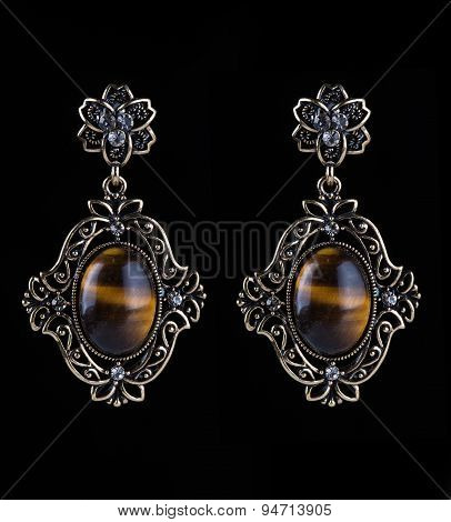 bronze earrings with jewels on the black