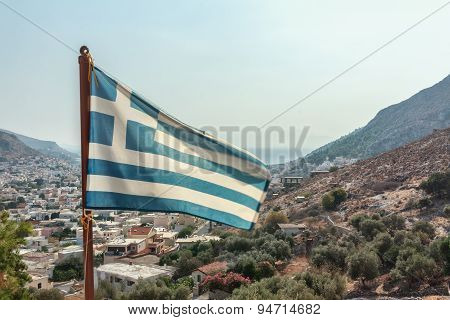 Flag of Greece waving at Pothia cityscape the capital of Kalymnos island background