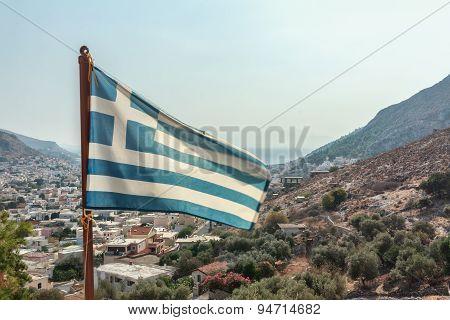 Flag of Greece waving at Pothia cityscape the capital of Kalymnos island background
