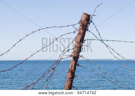 Old Barbed Wire Fence And Rusty Post Against Sea And Sky