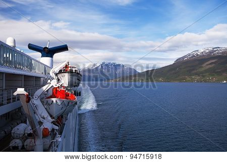 SOGNEFJORD, NORWAY - JUN 11 2015 : A cruise ship sails the Sognefjord, lifeboats at the ready.
