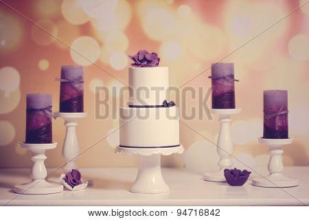 White Wedding Cake Sorounded By Purple Candles