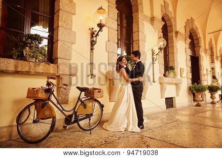 Bride and groom embracing near bicycle