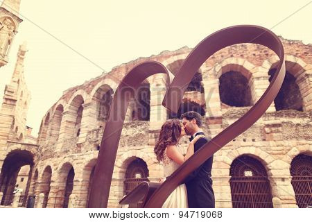 Bride And Groom Near Heart Shaped Sculpture