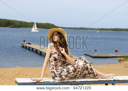 Floral Girl With Hat Sitting On Beach