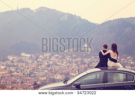 Bride And Groom Sitting On Their Car